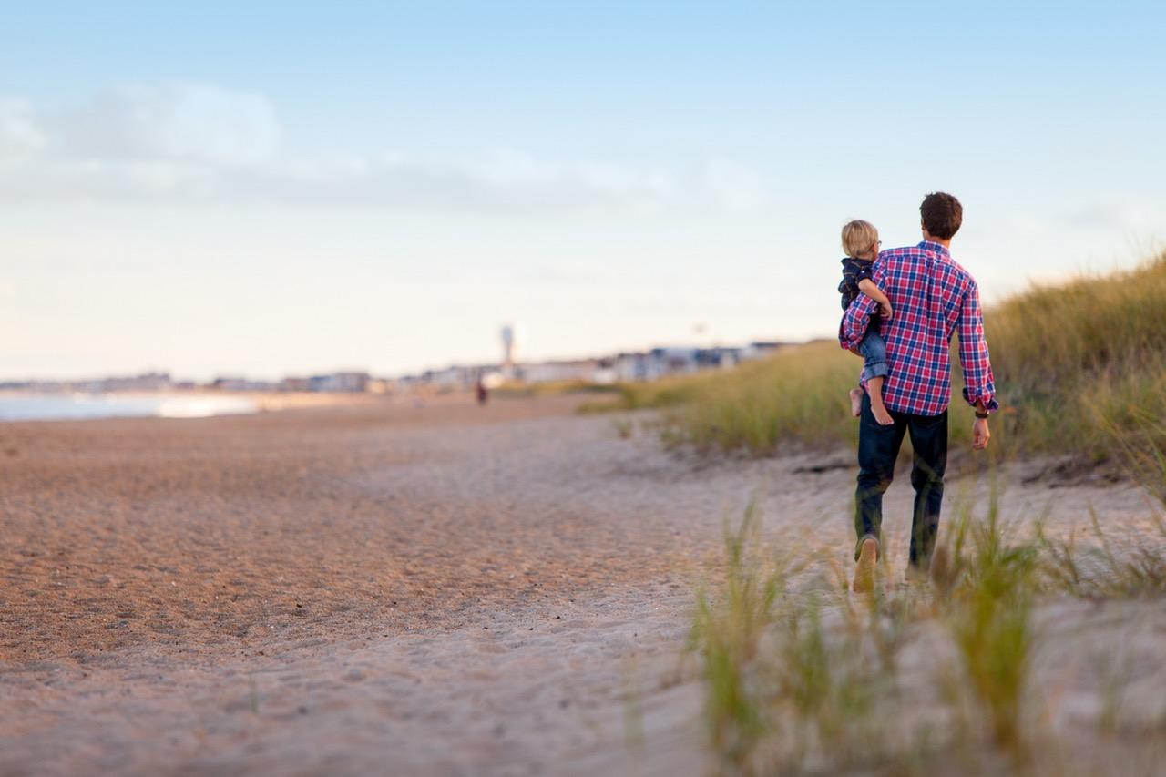 man boy on beach holding a little boy