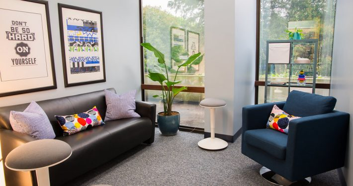 room with leather couch and a blue chair at center of excellence