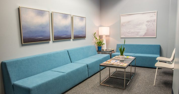 waiting room with blue couches and paintings on the wall at center of excellence